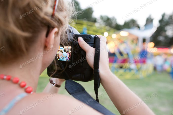 Unrecognizable woman photographing senior couple, fun fair