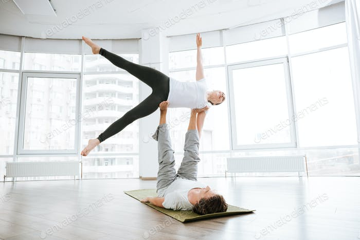 Happy man and woman doing acro yoga in pair