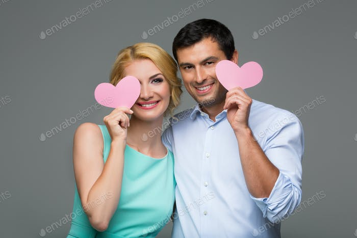 Beautiful couple holding pink hearts