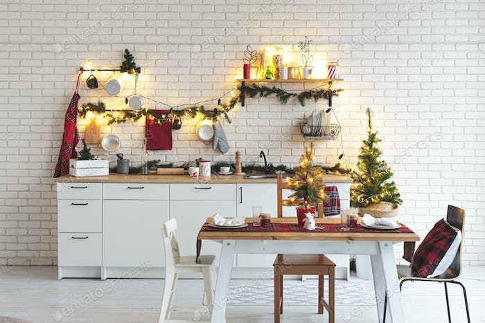 Interior white kitchen with lights and red christmas decorations