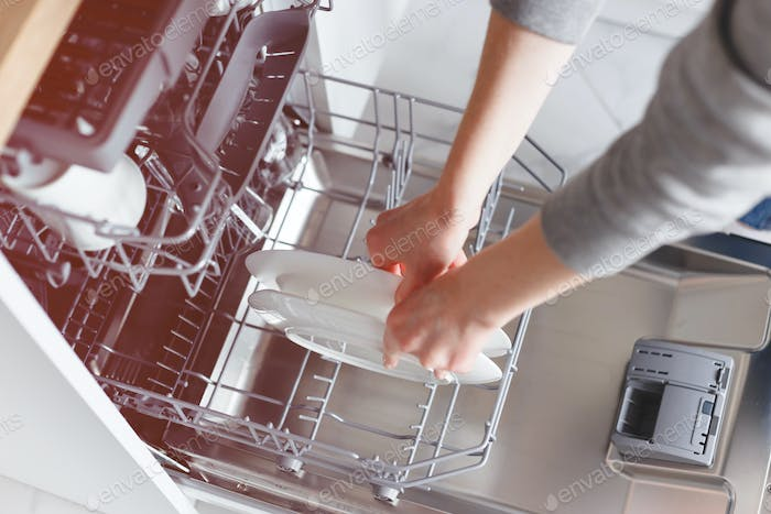 close-up of female hands putting dishes to the dishwasher.