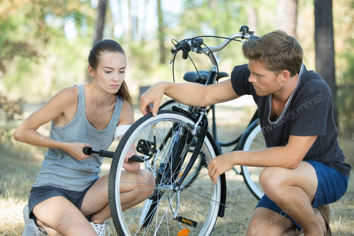 attractive girl inflating bike wheel with her boyfriend