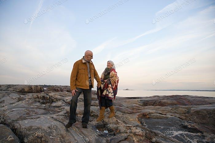 Mature couple walking over rocks