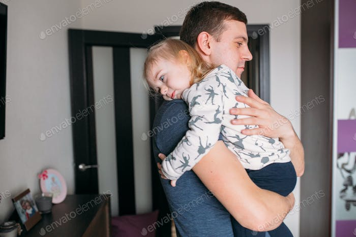 A little girl with a dad in her arms