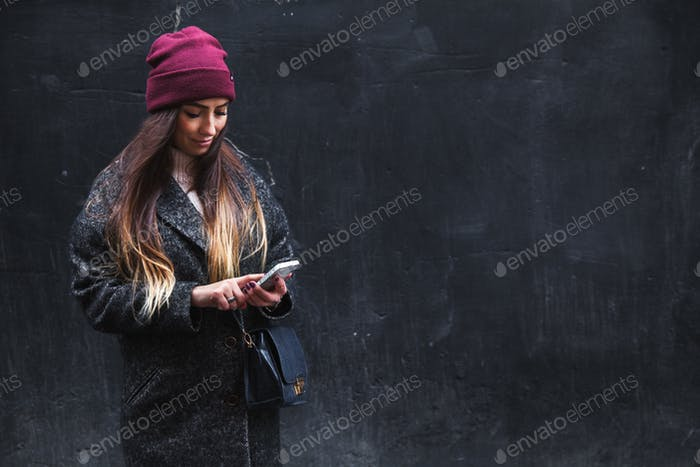 Happy beautiful woman enjoys on mobile phone on a black background