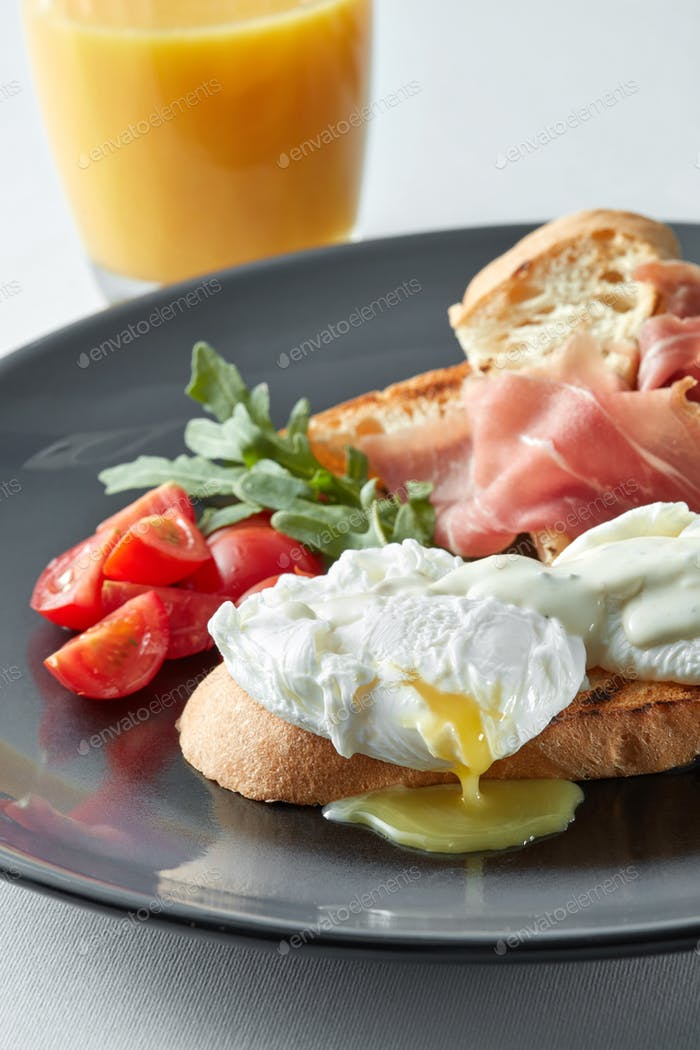 Eggs Benedict with ham and tomato