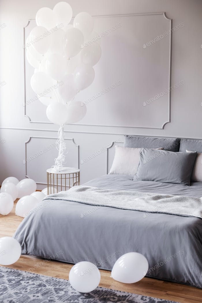 White balloons in stylish grey bedroom with comfortable king siz