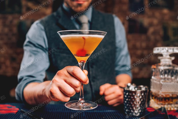 Bartender serving manhattan cocktail in martini glass