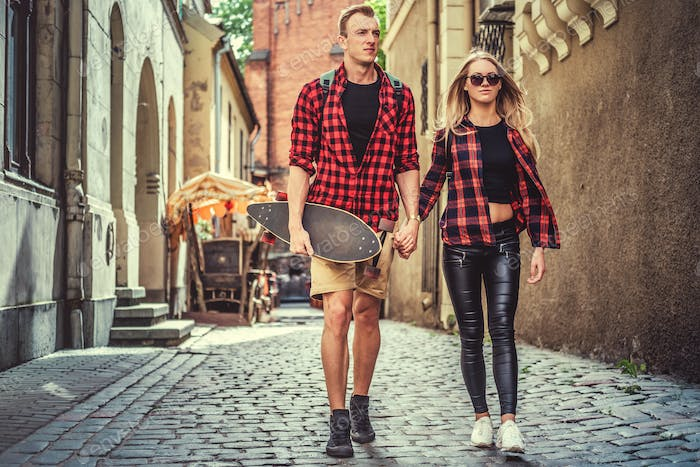 Cheerful longboarders couple in the city