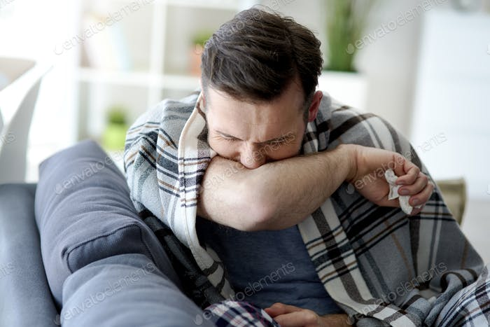 Man coughing in his elbow