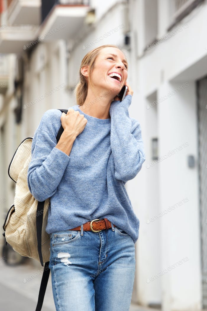 happy woman walking in city and talking on mobile phone