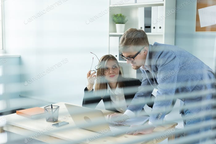 Business, teamwork and people concept - Portrait of serious man and attractive woman working at