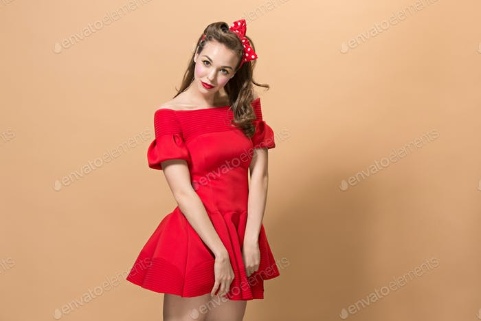 Beautiful young woman with pinup make-up and hairstyle. Studio shot on pastel background