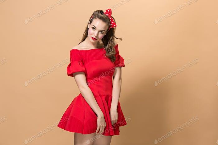 Красивая молодая женщина с пинап макияж и прическа. Студия выстрел на пастельных фоне