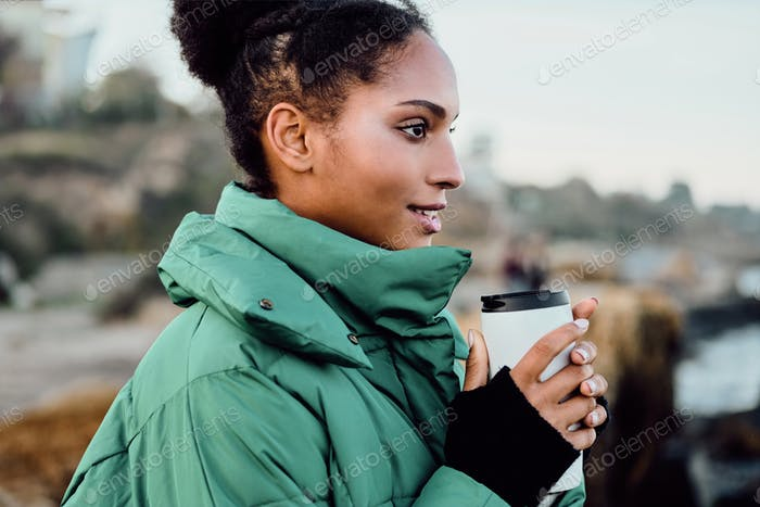 Pretty casual African American girl in down jacket with cup to go happily looking aside on seaside