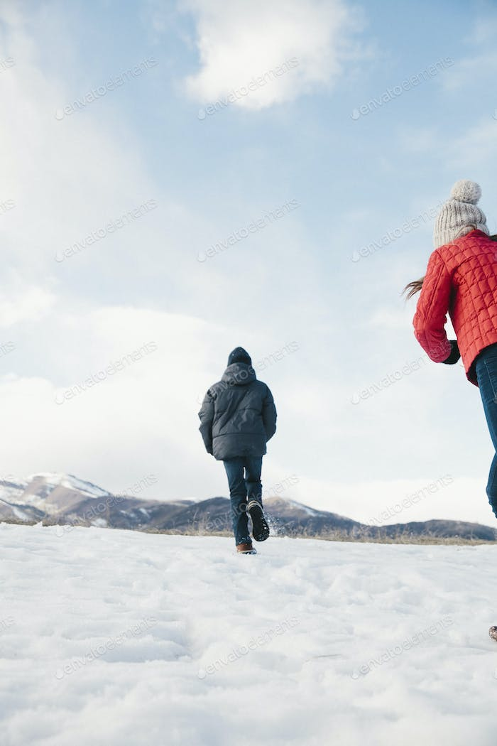 Two children, brother and sister running across the snow.