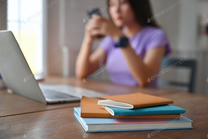 A notebook with a laptop on the table and a young woman using a smartphone on the back.