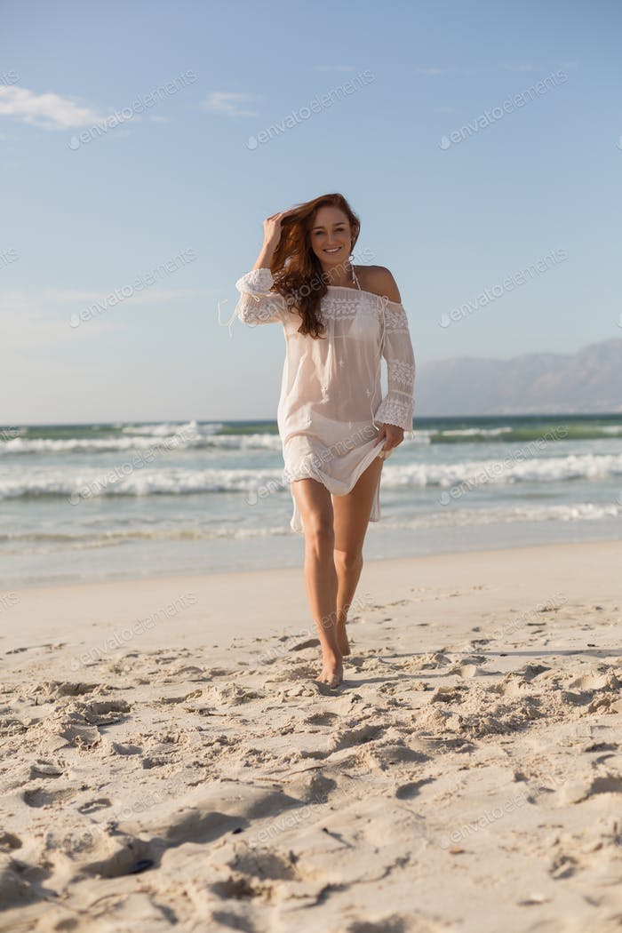 Portrait of beautiful young Caucasian woman walking on the beach in the sunshine. She is smiling