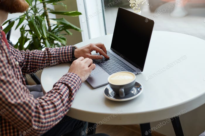 Close up in a cafe on a white table, men's hands are working on the keyboard