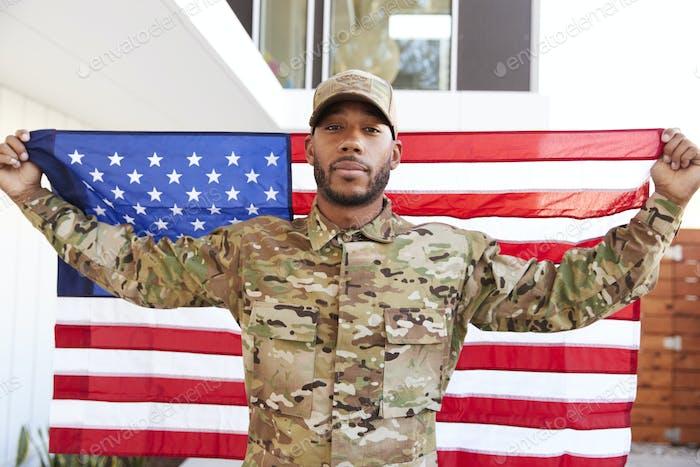Millennial black soldier standing outside modern building holding US flag