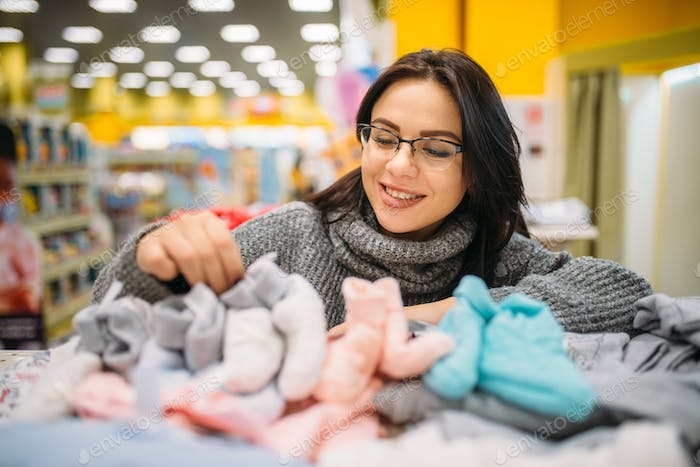 Future mother in glasses buys baby clothes