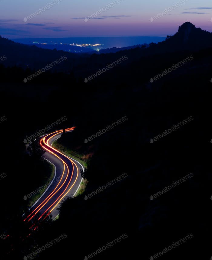 mountain road at night with cars moving fast (color toned image)