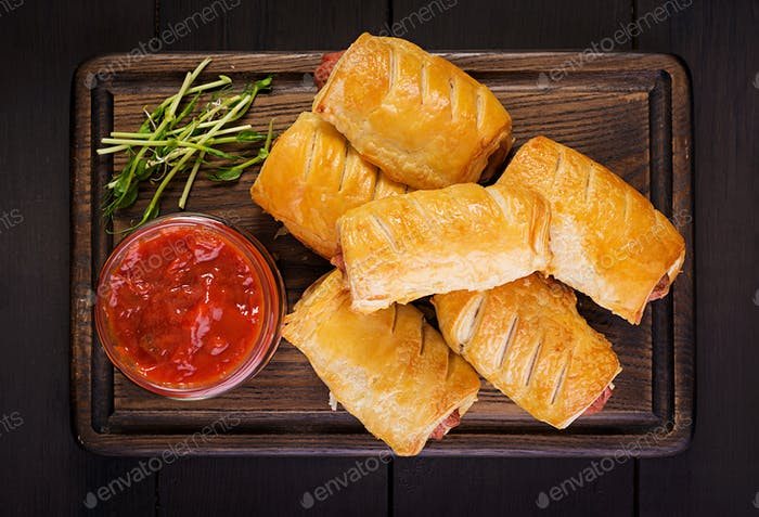 Sausage in the dough on a wooden board with tomato sauce. Top view