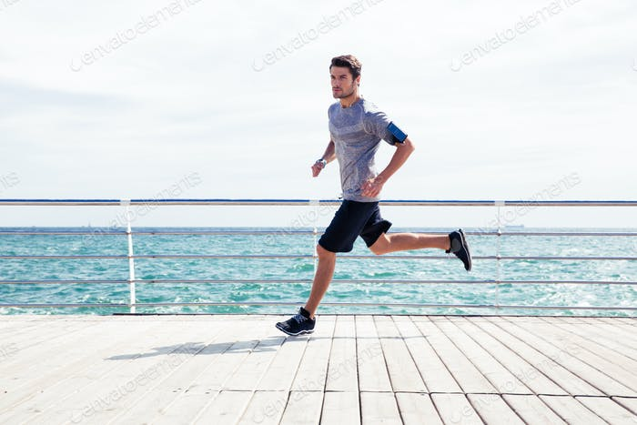 Sports man running outdoors near sea