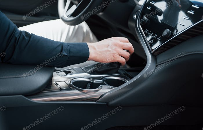 Close up view of a young man driving a car. Start a business trip. Test drive a new auto