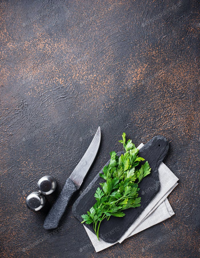 Culinary background with spices, knife, parsley and cutting boar