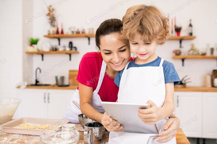 Affectionate young woman and her son with touchpad watching video recipe