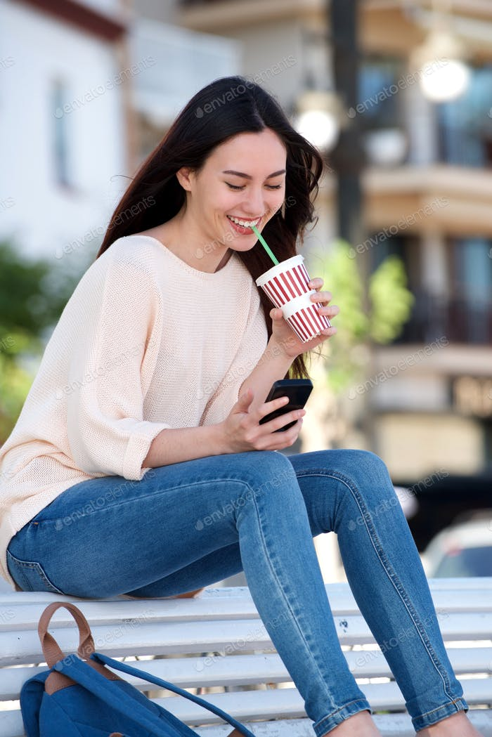 Happy woman sitting on bench with cellphone and drink