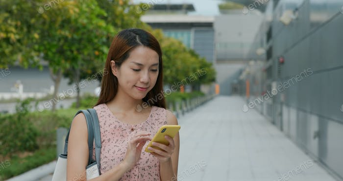 Woman uses mobile phone outdoors