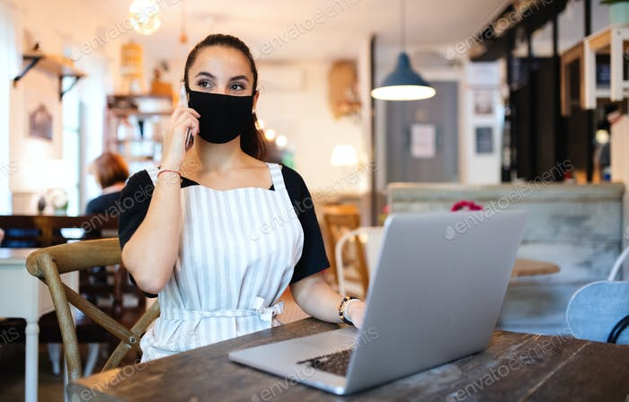 Young woman with apron, smartphone and laptop working in cafe
