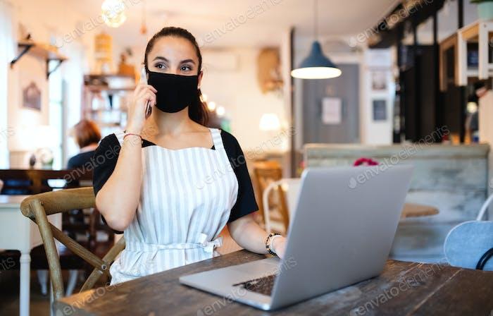 Junge Frau mit Schürze, Smartphone und Laptop arbeiten im Café