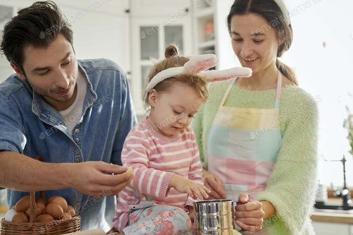 Little girl helping her parents with baking cookies