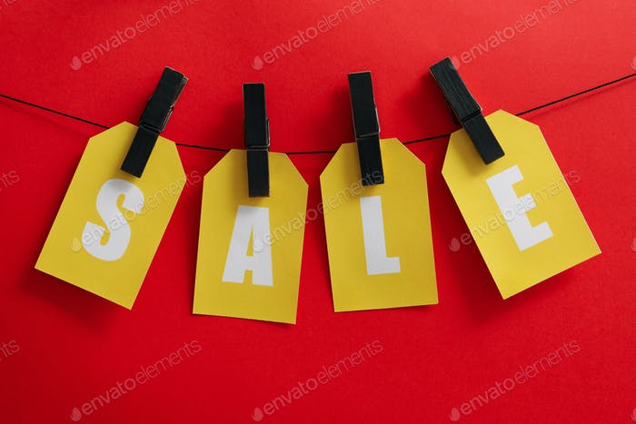 Text Sale hanging on the clothesline on red background