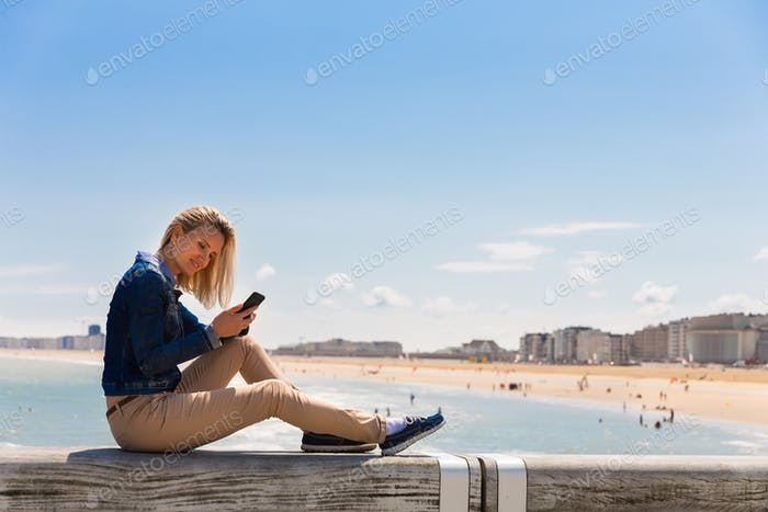 Female tourist sitting on pier, city beach, Europe
