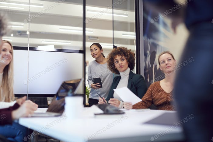 Businesswoman Arriving Late For Presentation By Colleague In Modern Office