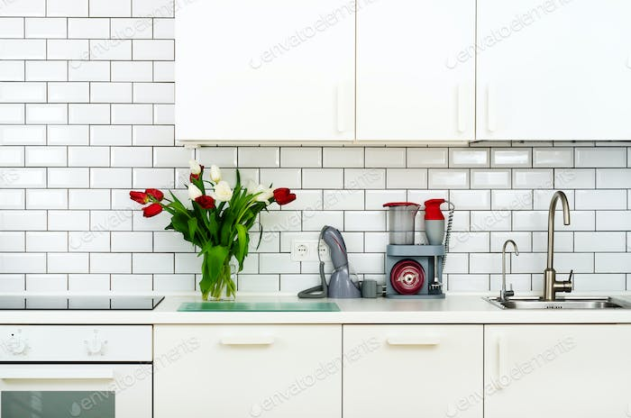 Fresh bouquet of red and white tulips on kitchen table. Detail of home interior, design