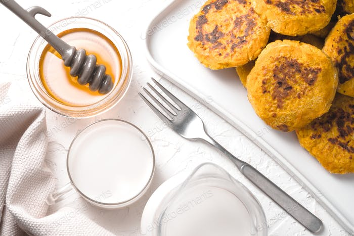 Hemp milk, pumpkin pancakes and honey on a white table