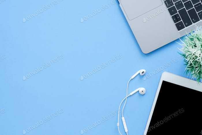 top view mockup photo of a working space with laptop, earphone and mock up tablet.