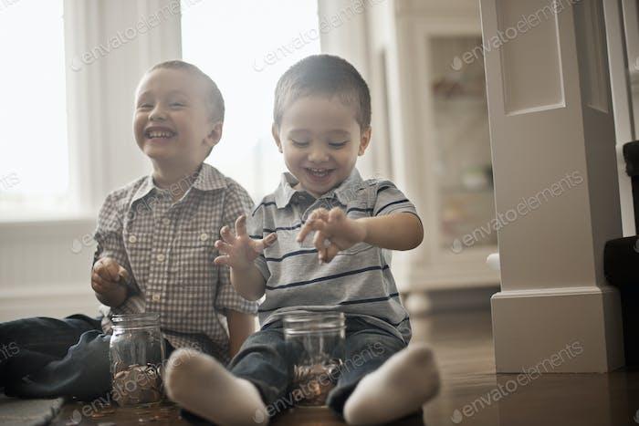 Zwei Kinder spielen mit Münzen und lassen sie in Gläser fallen.