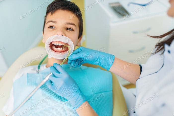 Boy in a dental cabinet, caries removal procedure