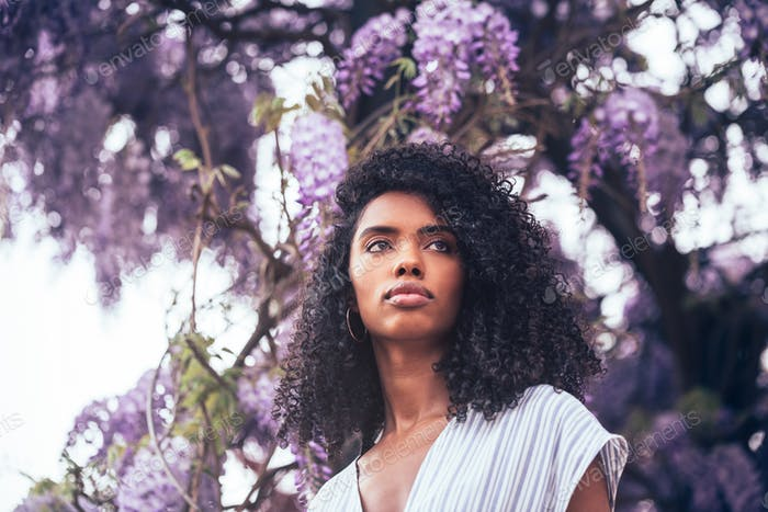 Thoughtful young black woman sitting surrounded by flowers