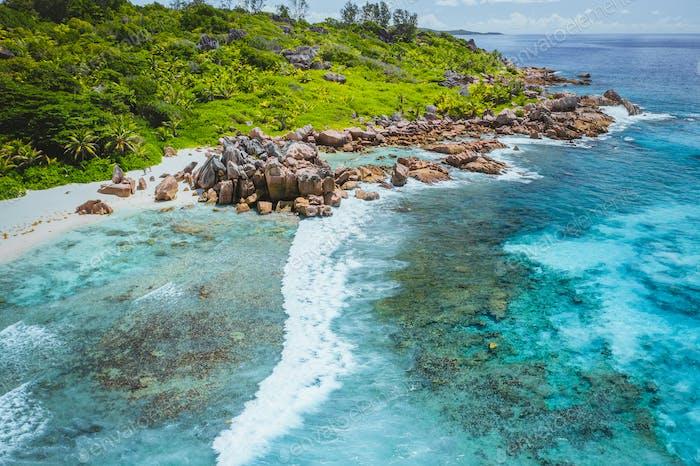 Tropical beach Anse Cocos. La Digue island. Seychelles. Drone aerial view of coastline with blue