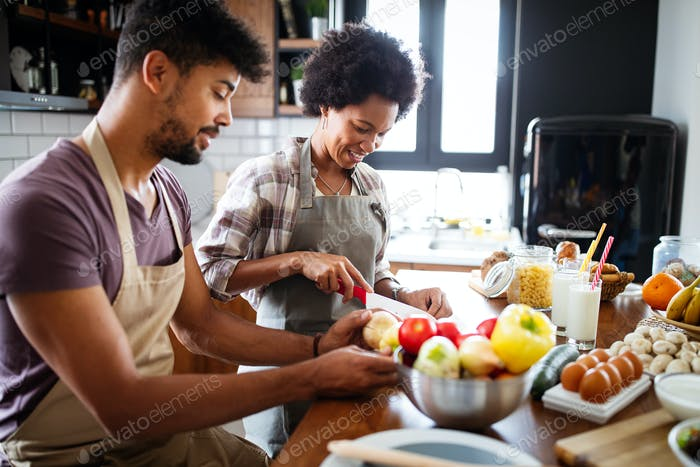 Beautiful young couple having fun and laughing while cooking in kitchen