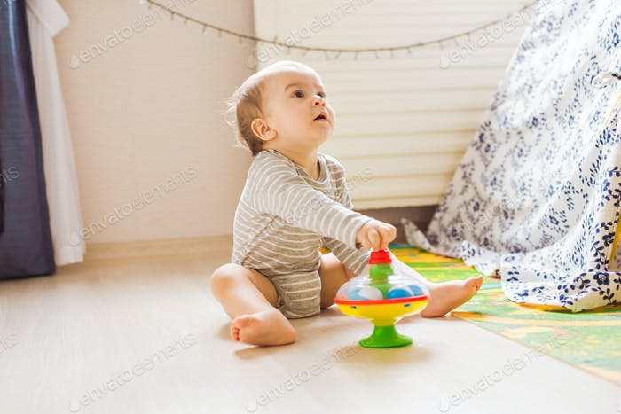 Baby boy plays in his room.