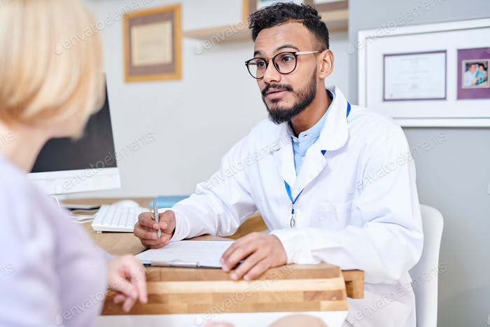 Middle-Eastern Doctor Consulting Female Patient