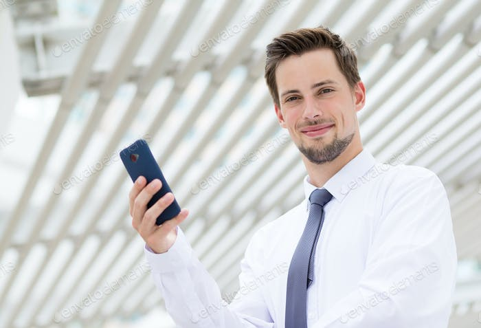 Caucasian businessman holding cellphone at outdoor